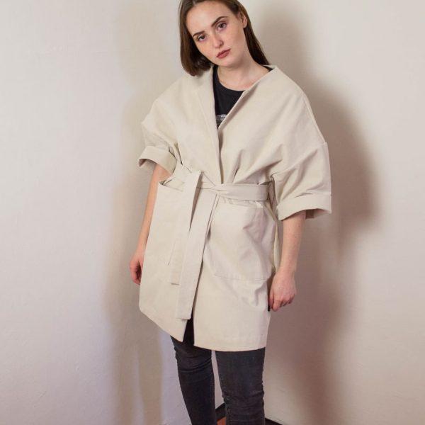 Dievča v krátkom béžovom kabáte zpredu
