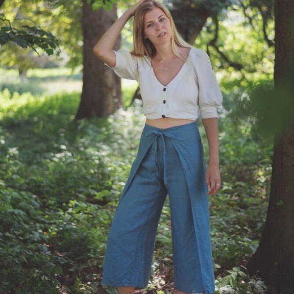Modelka oblečená v modrých zavinovacích ľanových nohaviciach miljo