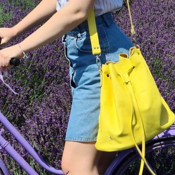 Žltá kožená kabelka typu vrece v outfite s modrou sukňou