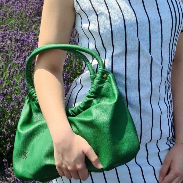 Zelená kožená kabelka do ruky od SussesBag v outfite s bielo-čiernymi šatami